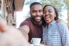 Pares africanos sonrientes que toman selfies juntos en un café de la acera foto de archivo libre de regalías