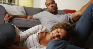 Pares afro-americanos bonitos que sentam-se no assoalho foto de stock