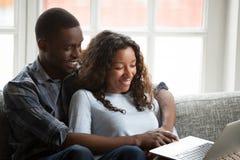 Pares afro-americanos de amor usando o portátil junto fotos de stock royalty free