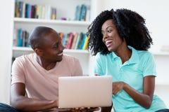 Pares afro-americanos de riso com computador imagens de stock royalty free
