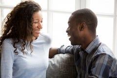 Pares afro-americanos de sorriso no amor que senta-se junto foto de stock