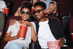 Pares afro-americanos felizes que olham o filme 3D Imagem de Stock