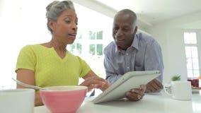 Pares afro-americanos maduros usando a tabuleta de Digitas em casa filme