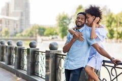 Pares afro-americanos novos de amor que abraçam na ponte foto de stock