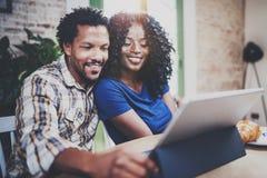 Pares afro-americanos novos de sorriso que têm a conversação em linha junto através da tabuleta de toque na manhã na sala de visi foto de stock
