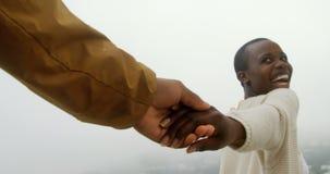 Pares afro-americanos que andam com em conjunto sobre a praia 4k video estoque