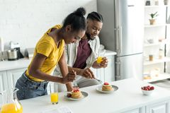 pares afro-americanos que comem panquecas e que bebem o suco de laranja fotografia de stock royalty free