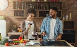 Pares afro-americanos que cozinham o jantar e que bebem o vinho tinto fotografia de stock