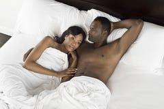 Pares afro-americanos que encontram-se na cama Fotografia de Stock