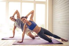 Pares afro-americanos que fazem a ioga fotografia de stock