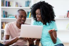 Pares afro-americanos que procuram o trabalho em linha com computador imagem de stock