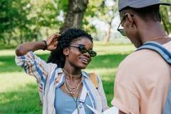 Pares afro-americanos que têm a conversação junto com o homem no parque imagem de stock