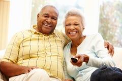 Pares afro-americanos superiores que olham a tevê Fotografia de Stock