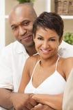Pares afroamericanos felices de la mujer que se sientan en casa Imagen de archivo libre de regalías