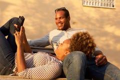 Pares afroamericanos felices junto en banco de parque fotos de archivo