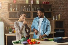 Pares afroamericanos felices que cocinan en cocina del desván foto de archivo libre de regalías
