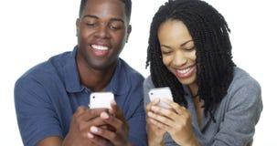 Pares afroamericanos jovenes que mandan un SMS en los teléfonos celulares junto