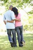 Pares afroamericanos jovenes románticos que caminan en parque Foto de archivo