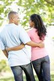 Pares afroamericanos jovenes románticos que caminan en parque Fotografía de archivo