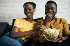 pares afroamericanos jovenes sonrientes que comen las palomitas mientras que se sienta en el sofá imagen de archivo libre de regalías