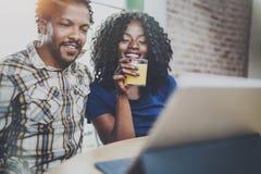 Pares afroamericanos jovenes sonrientes que tienen conversación en línea junto vía la tableta de tacto en la mañana en sala de es fotografía de archivo libre de regalías