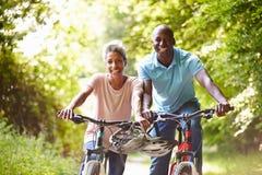 Pares afroamericanos maduros en paseo del ciclo en campo Imagen de archivo libre de regalías