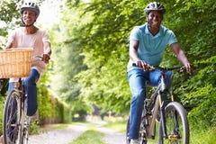 Pares afroamericanos maduros en paseo del ciclo en campo Imágenes de archivo libres de regalías