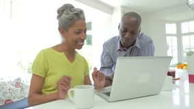 Pares afroamericanos maduros usando el ordenador portátil en casa metrajes