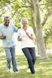 Pares afroamericanos mayores que corren en parque Foto de archivo libre de regalías