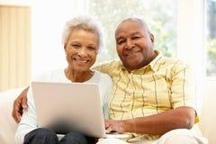 Pares afroamericanos mayores usando el ordenador portátil fotos de archivo libres de regalías