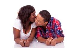 Pares afroamericanos negros jovenes felices que se acuestan en el floo Imagenes de archivo