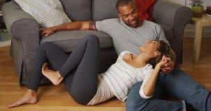 Pares afroamericanos que hablan en piso Imagen de archivo libre de regalías