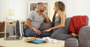 Pares afroamericanos que hablan junto en el sofá Imagen de archivo libre de regalías
