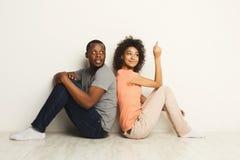 Pares afroamericanos que miran para arriba, sentándose en piso Fotografía de archivo