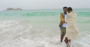 Pares afroamericanos que se divierten junto en la playa 4k metrajes