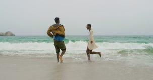 Pares afroamericanos que se divierten junto en la playa 4k almacen de metraje de vídeo