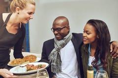Pares afroamericanos que son servidos la cena fotografía de archivo