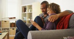 Pares afroamericanos usando los dispositivos en el sofá Fotos de archivo libres de regalías
