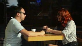 Pares agradáveis novos que sentam-se no café envolvido no chá bebendo geral acolhedor História de amor de uma menina e de um meni video estoque