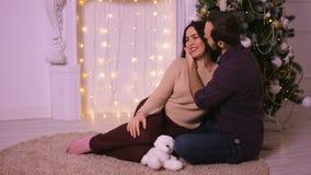 Pares agradables del amor que se sientan en la alfombra cerca de la chimenea Mujer y hombre que celebran la Navidad almacen de video