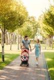 Pares agradables jovenes que caminan con el bebé en carro imagenes de archivo