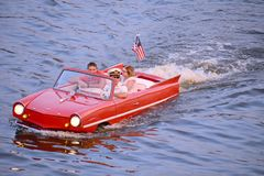 Pares agradables que disfrutan de paseo anfibio rojo del coche en el área de Buena Vista del lago foto de archivo