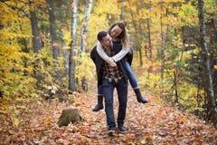 Pares agradables que se divierten en parque del otoño Imágenes de archivo libres de regalías