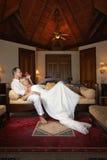 Pares agradáveis que encontram-se no sofá na casa de campo bonita Imagem de Stock