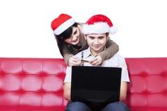 Pares aislados de la Navidad que hacen compras en línea Imágenes de archivo libres de regalías