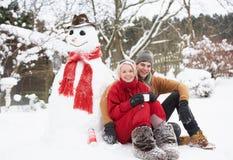 Pares al lado del muñeco de nieve con la bebida caliente Imagenes de archivo