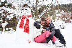 Pares al lado del muñeco de nieve con la bebida caliente Imágenes de archivo libres de regalías