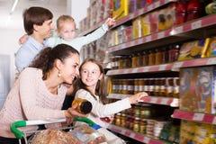 Pares alegres com as crianças pequenas que compram o doce Imagem de Stock Royalty Free