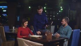Pares alegres con el menú en un restaurante que hace orden almacen de metraje de vídeo
