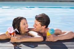 Pares alegres con las bebidas en piscina Foto de archivo libre de regalías